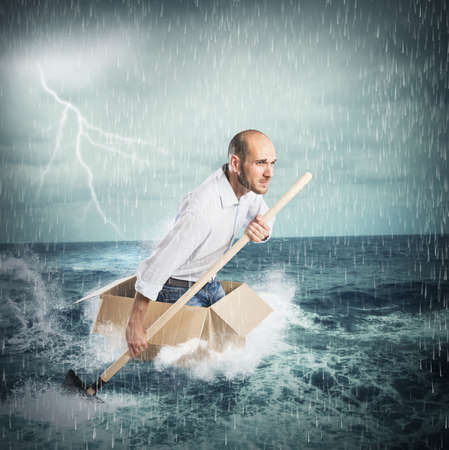 preoccupied: Businessman surfs on a cardboard during storm Stock Photo