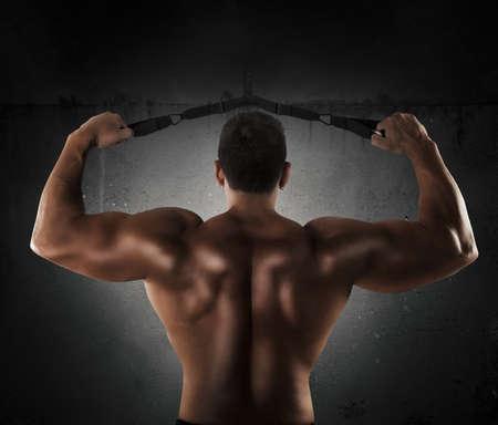muscle: El hombre entrena a los músculos de los hombros con trx