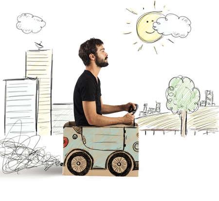 Boy driving cardboard car in drawing city