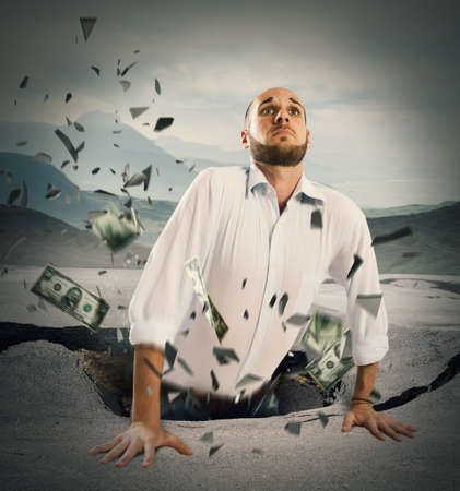 economic depression: Businessman falls in a break of asphalt Stock Photo