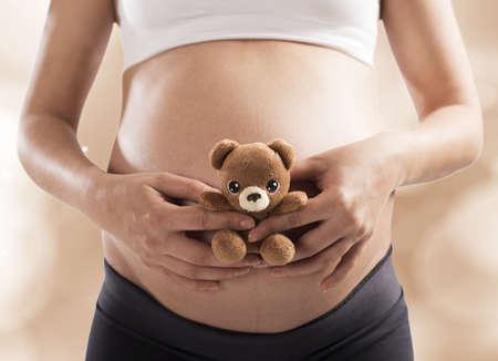 Liebevolle schwangere Frau mit kleinen Teddybären Standard-Bild