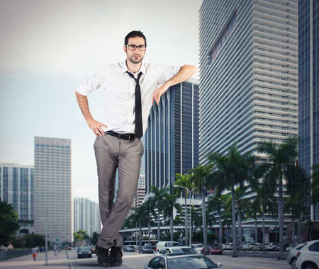 Giant successful businessman leaning against a skyscraper