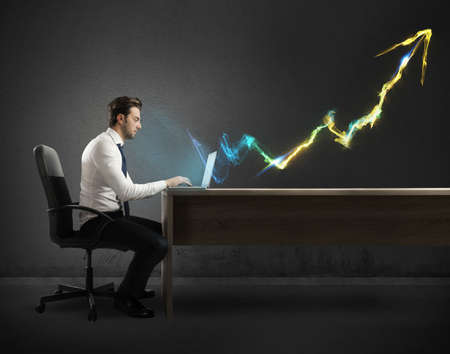 Businessman working at computer with light arrow