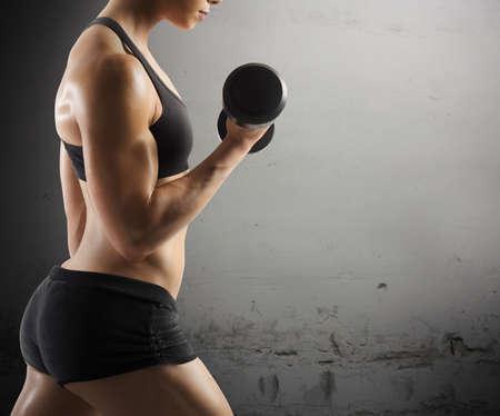 pesas: Atlético entrenamiento mujer muscular con el fondo del grunge Foto de archivo
