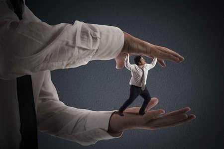 dominacion: Las grandes manos que aplastan un hombre peque�o Foto de archivo