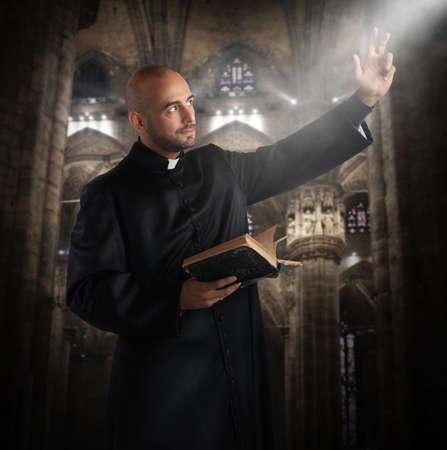Priester bidt in de kerk met bijbel