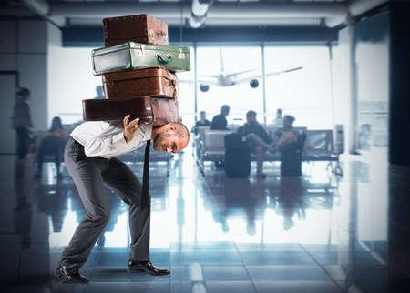 空港内の非常に多くのスーツケースを持ったビジネスマン
