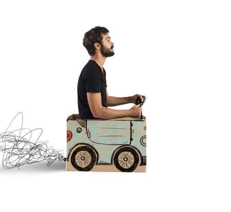 Jongen besturen van een nep ontworpen kartonnen auto