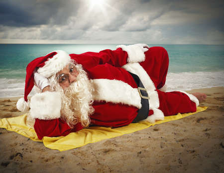 santaclaus: Santaclaus relaxing at the beach on towel Stock Photo