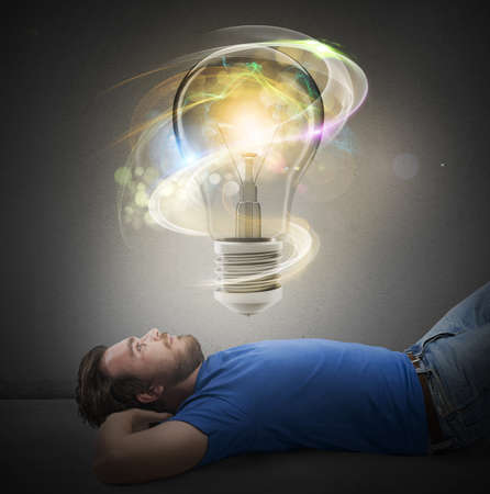 intuition: Man lying thinks with a big lightbulb Stock Photo