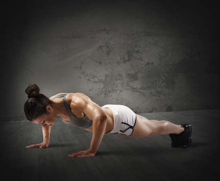 forceful: Muscular woman is training doing push up Stock Photo