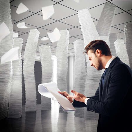 Stressed businessman analyzes mountains of work documents