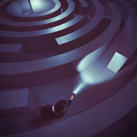 worried businessman: Man with flashlight in a dark maze Stock Photo