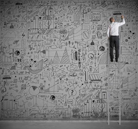 estadistica: Hombre de negocios en un dibujo a escala en la pared Foto de archivo