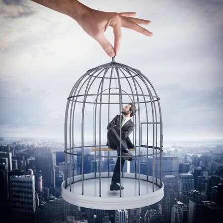 obedecer: Hombre de negocios sentado en una jaula de p�jaros Foto de archivo