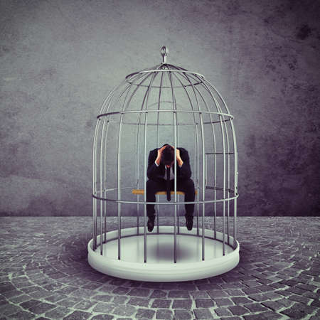 jailed: Alone desperate businessman in a bird cage Stock Photo