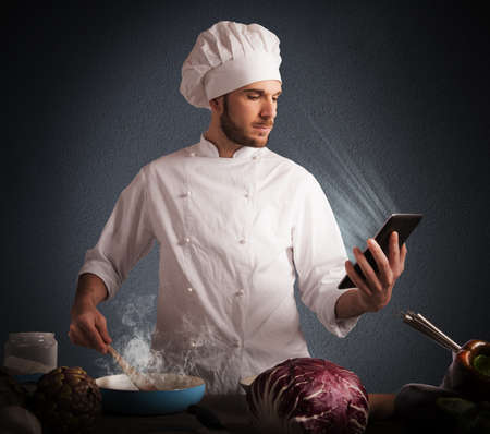 Man chef cooking while reading on tablet