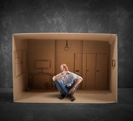 vision futuro: Hombre de negocios sentado en la oficina diseñada en cartón Foto de archivo