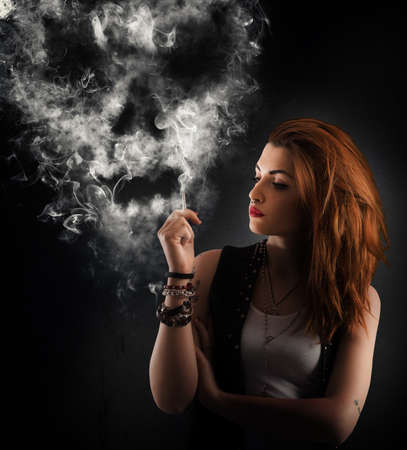 Girl smokes a cigarette forming a skull