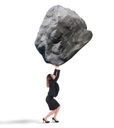 Businesswoman holding up a big rock heavy Stok Fotoğraf