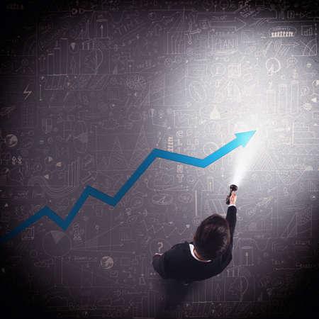 biznes: Biznesmen świeci z pochodnią strzałką