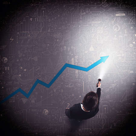 increase success: Businessman lights with a torch an arrow Stock Photo