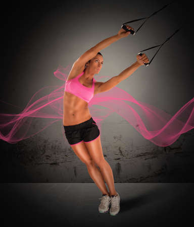 potency: Woman fitness instructor training with the TRX Stock Photo