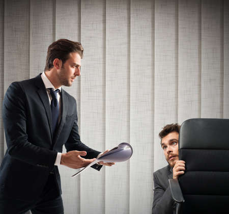 burdensome: Fearful of boss employee is behind a chair Stock Photo