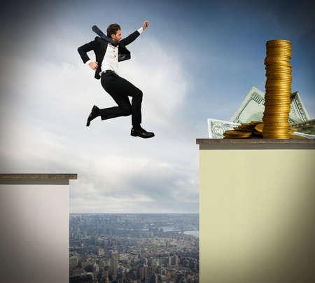 Determined businessman jumps risky to get money Standard-Bild