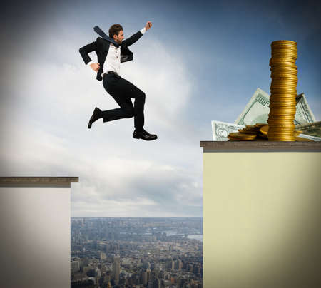 Determined businessman jumps risky to get money Stockfoto