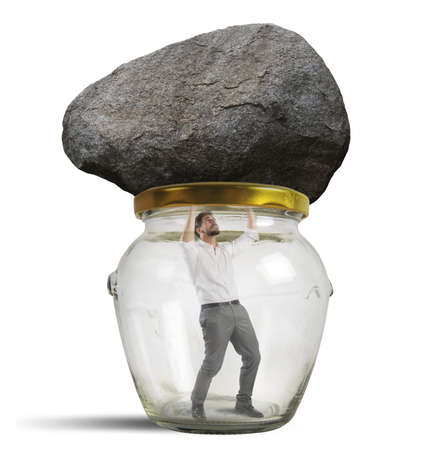 trapped: Man trapped in a jar with rock Stock Photo