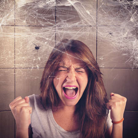 Girl screaming trapped in a spider web Standard-Bild