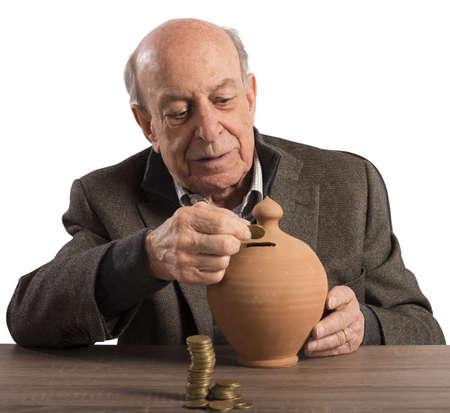 pension: Old man keeps pension in a piggybank