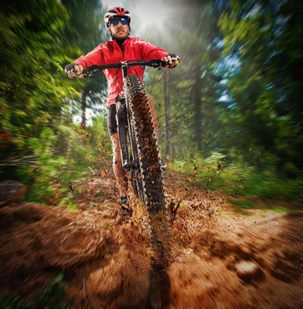 sunrise mountain: Extreme cyclist pedals on the ground unpaved Stock Photo