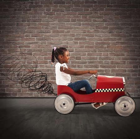 imaginacion: Niña feliz que conduce un coche de juguete Foto de archivo