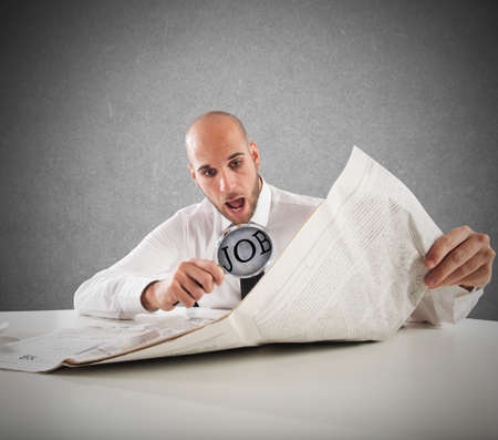 wonderment: Businessman reading the newspaper with magnifying lens