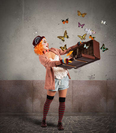 open suitcase: Clown opens a suitcase which emerges butterflies Stock Photo
