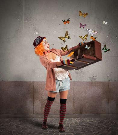 mujer con maleta: Payaso abre una maleta que emerge mariposas Foto de archivo