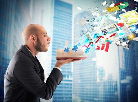 cognicion: El hombre de negocios que sopla sobre un libro de negocios de magia