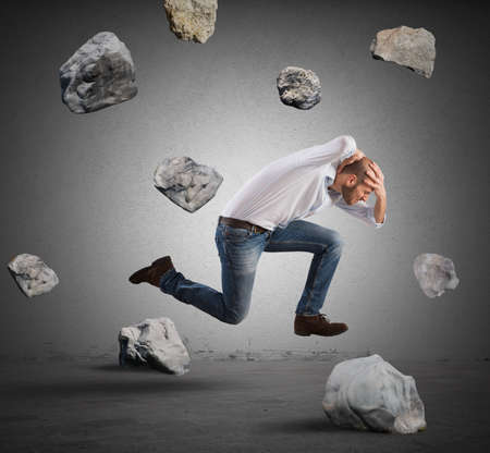 fear: Running businessman escapes from crisis with stone storm Stock Photo
