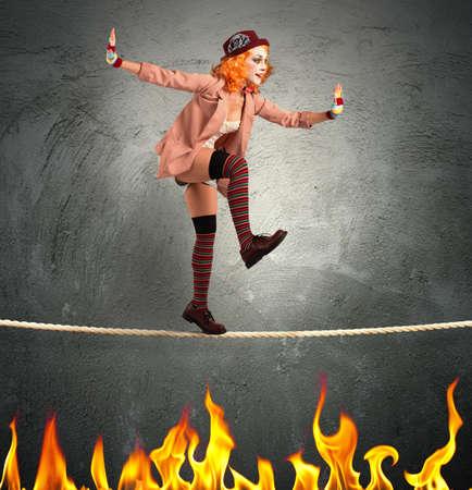 Clown balanceren op een touw over het vuur Stockfoto