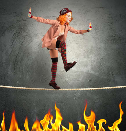 Clown balancing on a rope over fire Stock Photo