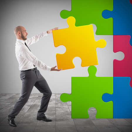 Businessman complete a puzzle inserting last piece Stock Photo