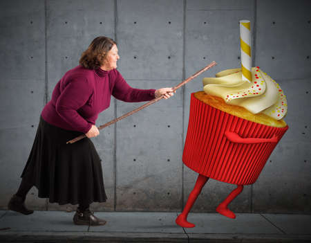 reduce: Fat woman hit with stick a cupcake Stock Photo