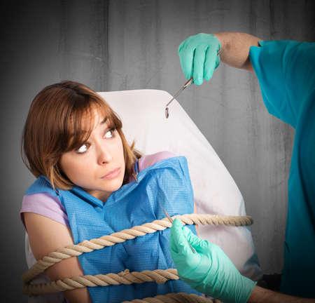 gefesselt: Erschrockenes Mädchen an den Stuhl gefesselt Zahnarzt