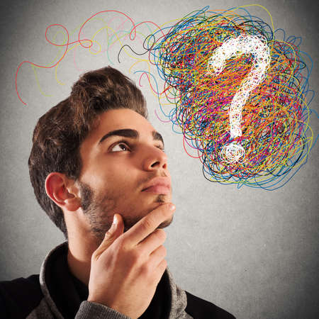 incertitude: Boy with thoughtful expression and question mark Stock Photo