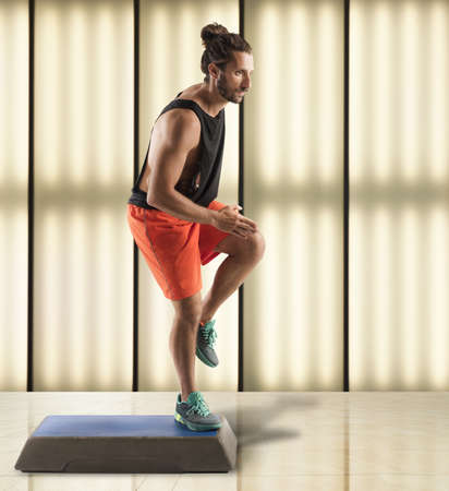 step fitness: Instructor man does fitness with a step