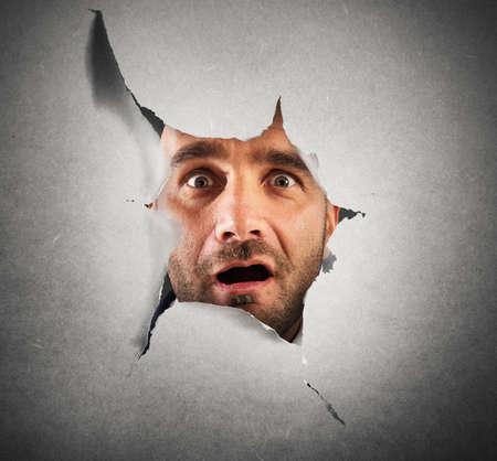 Man peeking through a hole something shocking 版權商用圖片