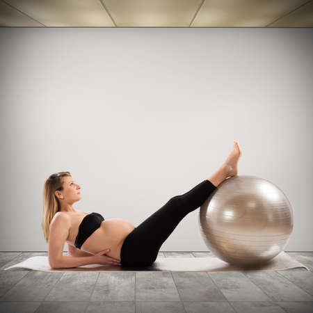 pregnant woman yoga: Pregnant woman does fitness exercises with ball Stock Photo