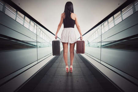 globetrotter: Woman rise with an escalator with baggage Stock Photo